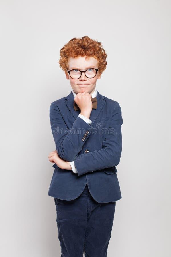 Tänkande barnpojke med den ljust rödbrun hårståenden arkivbild