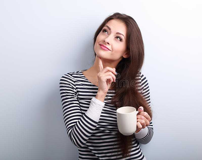 Tänkande bekymrad ung kvinna som ser upp med koppen kaffe arkivbild