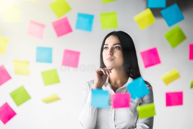 Tänkande bruksanmärkningar för idérik kvinna som delar idé Affärskontor arkivbild