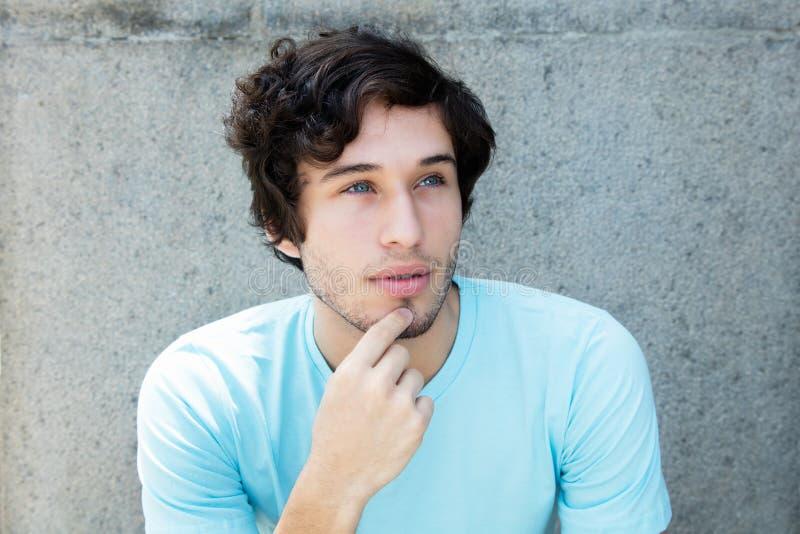 Tänkande caucasian ung vuxen man med blåa ögon royaltyfria bilder