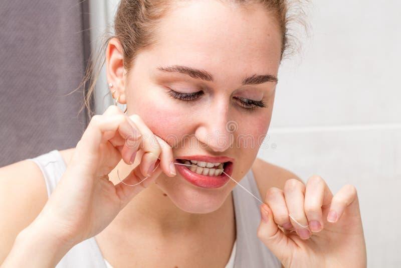 Tänkande härlig ung kvinna som ner ser och att rymma en tandtråd royaltyfria foton