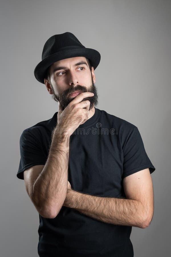 Tänkande hipster som bär den svarta t-skjortan och hatten som slår skägget som bort ser royaltyfria foton
