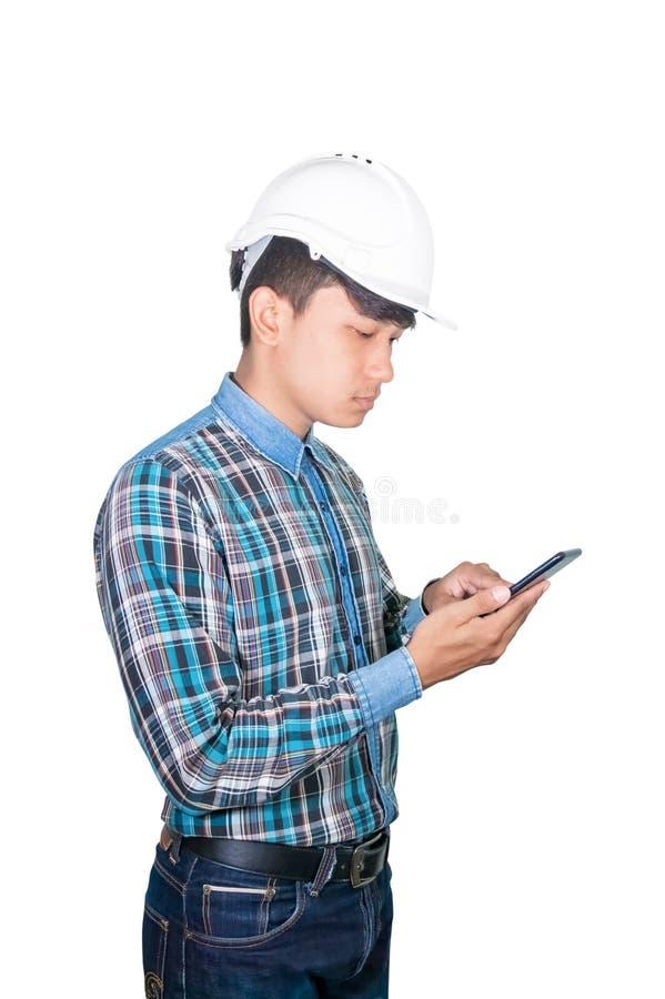 Tänkande kommando för affärsmantekniker med mobiltelefonen med 5g nätverket, snabb mobil internet och bär den vita säkerhetshjälm arkivfoto