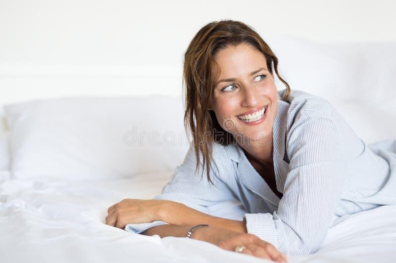 Tänkande kvinna på säng arkivbild