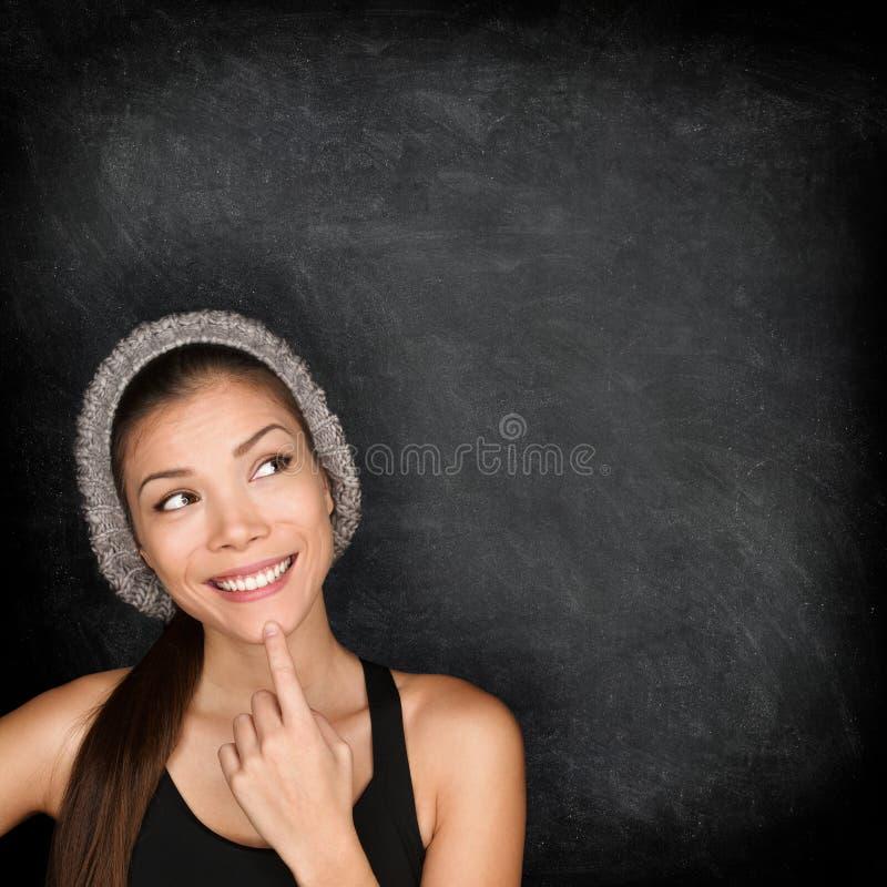 Tänkande kvinna vid svart tavla royaltyfria bilder