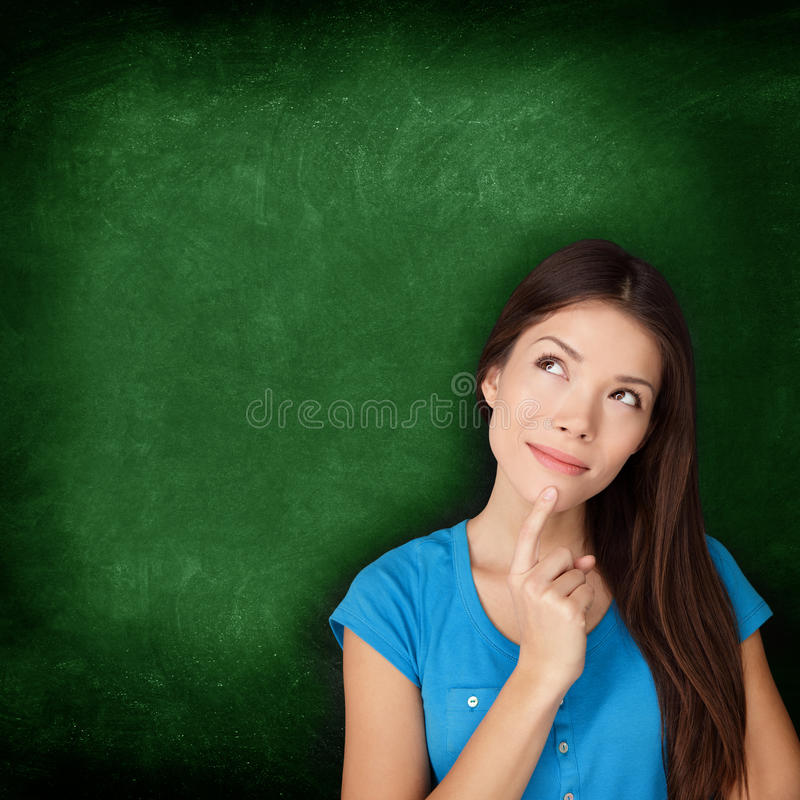 Tänkande kvinnastudent eller lärare med svart tavla arkivfoto