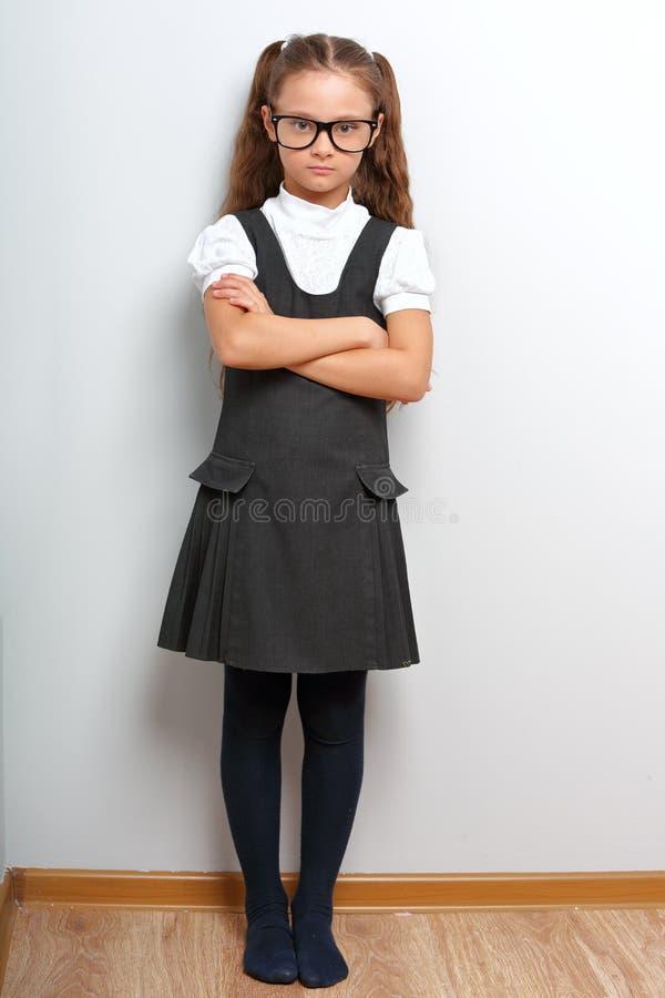 Tänkande lycklig le elevflicka i modeglasögon med vikta armar i skolalikformig fotografering för bildbyråer