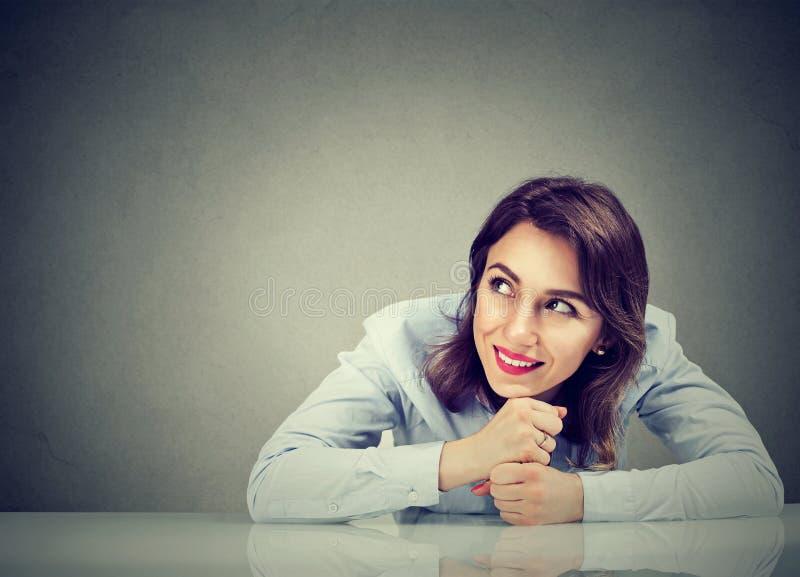 Tänkande lyckligt sammanträde för affärskvinna på skrivbordet som ser till sidan royaltyfria bilder