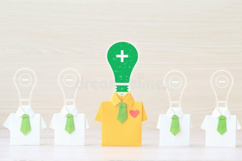 Tänkande positivt begrepp, gul skjorta för origami med bandet och ljus kula med positivt och negativt tänka på wooderbakgrund arkivfoton