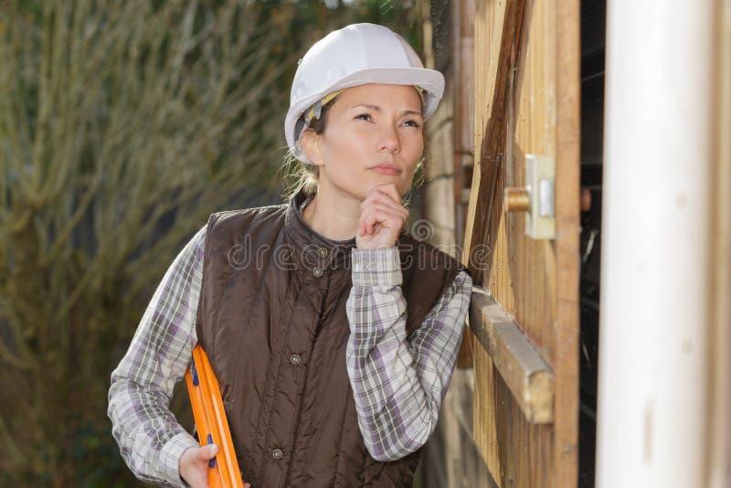 Tänkande renoveringidéer för kvinnlig arbetare royaltyfri foto