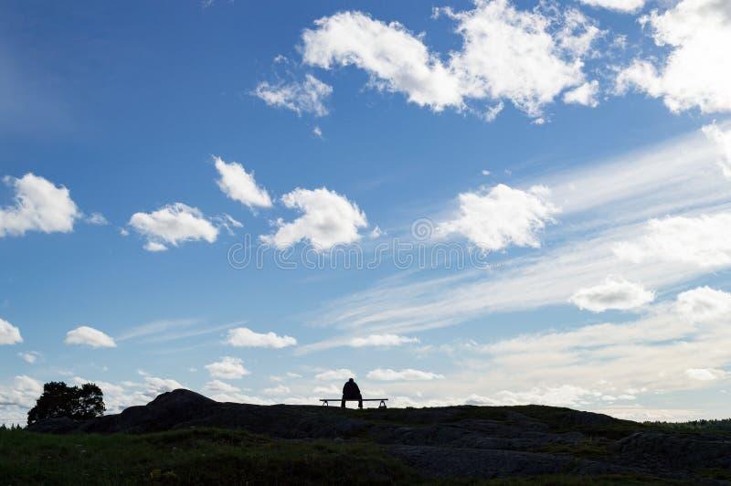 Tänkande sittande bänk för konturpersonman på molnig himmel för horisontlandskap royaltyfria foton