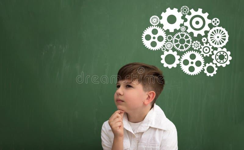 Tänkande skolpojke med idékläckning arkivfoto