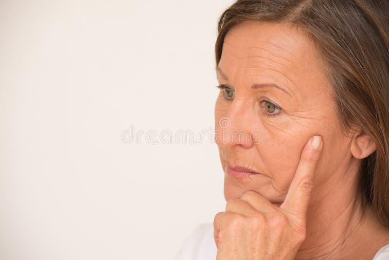 Tänkande stående för bekymrad mogen kvinna arkivfoto