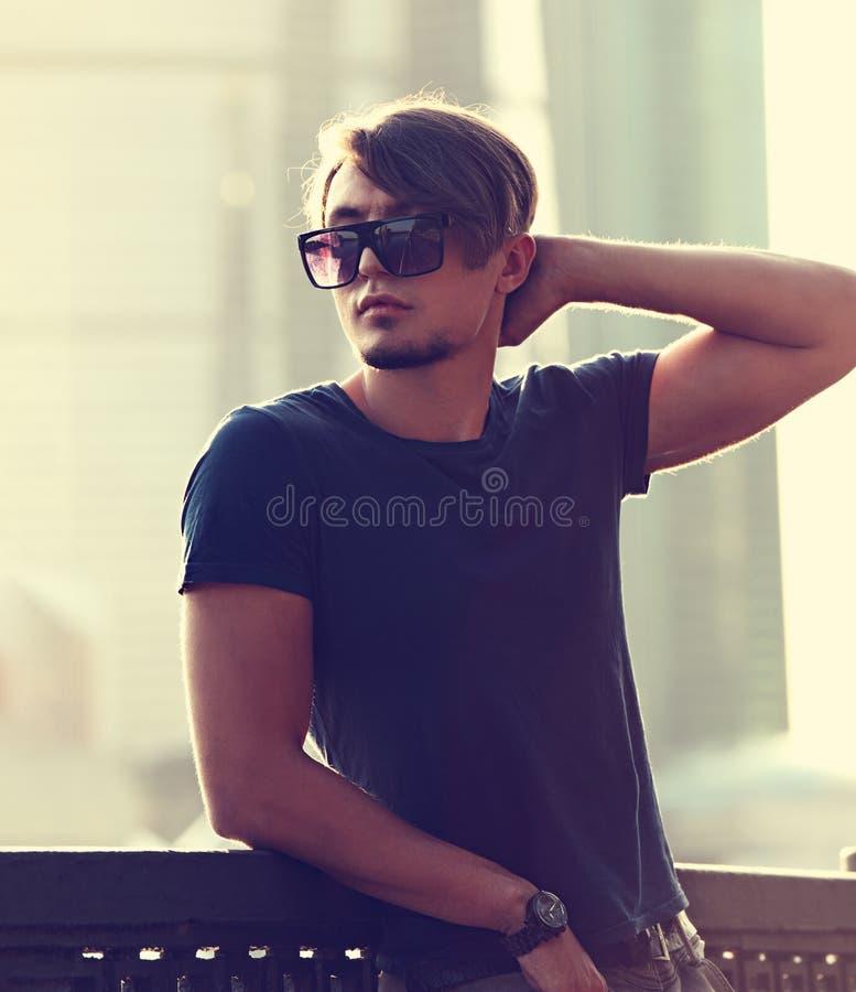 Tänkande stilig ung man i modesolexponeringsglas som ser på ci royaltyfria foton