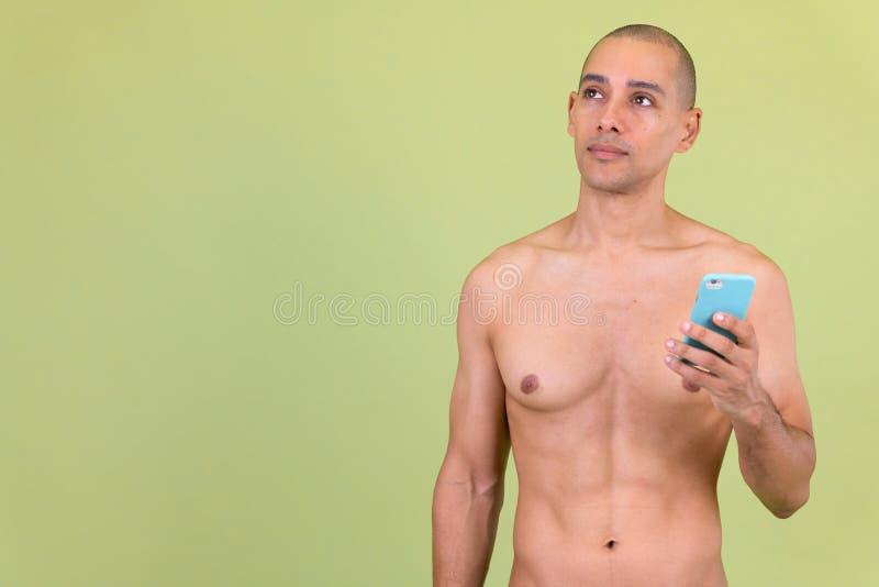Tänkande stund för stilig skallig mång- etnisk man genom att använda den shirtless telefonen fotografering för bildbyråer