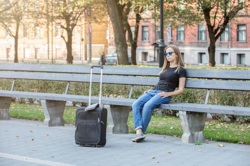 Tänkande turist- kvinna som sitter på bänken i parkera royaltyfri fotografi
