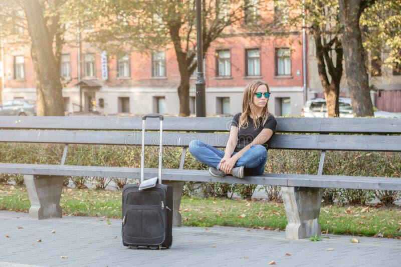 Tänkande turist- kvinna som sitter på bänken i parkera royaltyfria foton