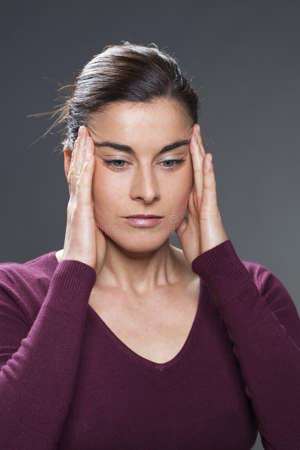 Tänkande ung kvinna som masserar hennes tempel för migränbehandling eller att släta för hud arkivbild