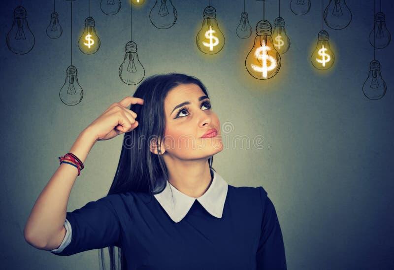 Tänkande ung kvinna som ser upp på ljusa kulor för dollaridé ovanför huvudet fotografering för bildbyråer