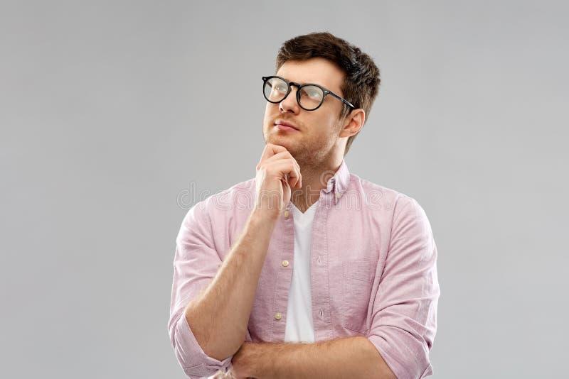 Tänkande ung man i exponeringsglas över grå bakgrund royaltyfri foto