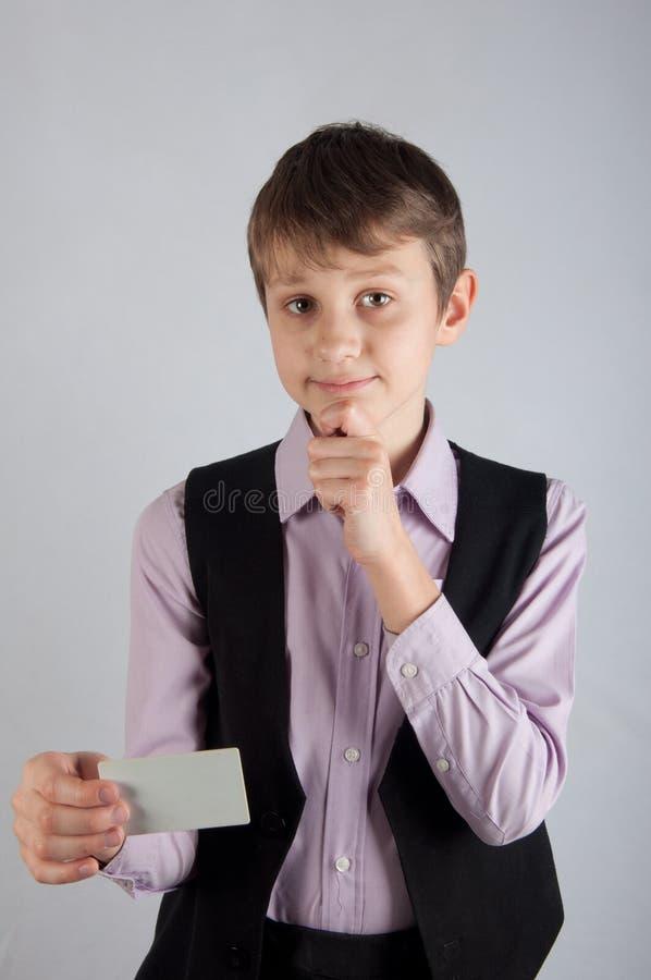 Tänkande unge i purpurfärgad hållande kreditkort för skjorta och för balsckwaistcoat på grå bakgrund royaltyfri fotografi
