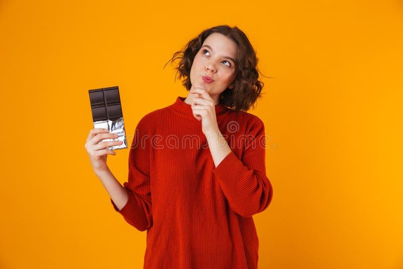 Tänkande ungt nätt posera för kvinna som isoleras över gul väggbakgrund som rymmer choklad royaltyfri foto