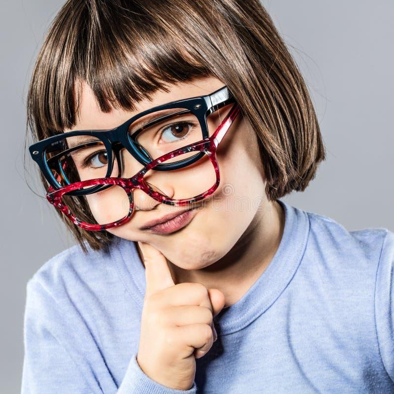 Tänkande uppnosig liten unge som försöker många glasögon som tvekar för val royaltyfri fotografi