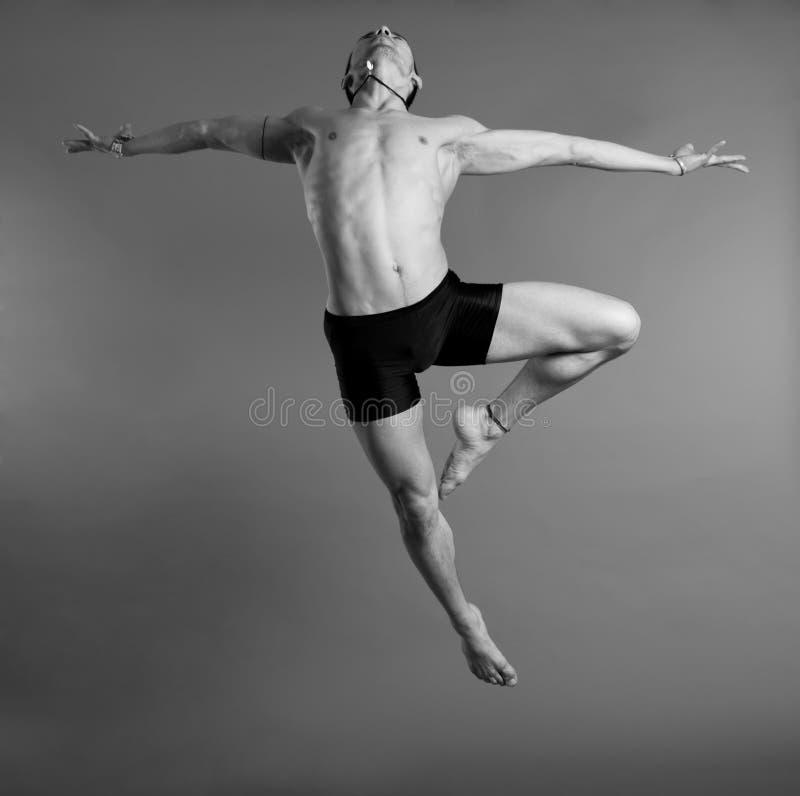 Tänzer, der über grauen Hintergrund springt stockfotos