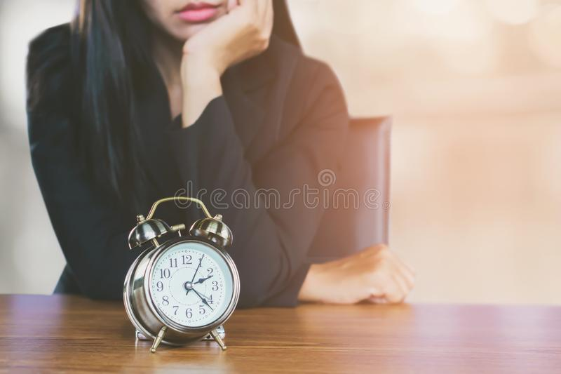 Tärande tidbegrepp med asiatisk känsla för affärskvinna som tröttas och borras se ringklockan på skrivbordet arkivfoto