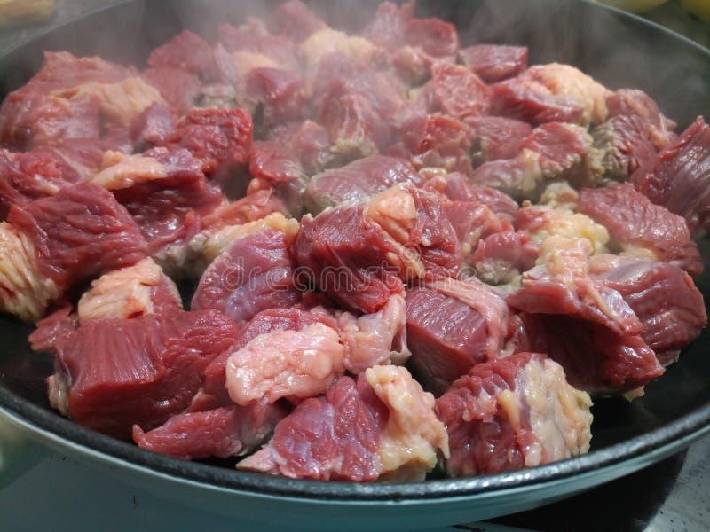 Tärnad nötköttmatlagning i en järnensemblepanna fotografering för bildbyråer