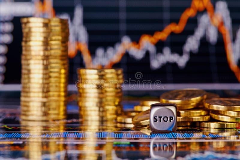 Tärnar kuben med uttryckaSTOPPET, downtrendbuntar av guld- myntar arkivbild