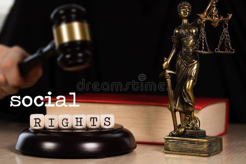 Tärnar SOCIALA RÄTTER för ordet som komponeras av trä Träauktionsklubba och staty av Themis i bakgrunden royaltyfri fotografi