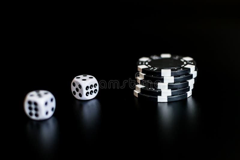 Tärningen och den monokromma kasinot gå i flisor på svart bakgrund royaltyfria foton