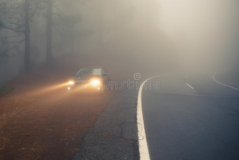 Tät mistskogväg och bil på vägrenen med ljusa strålar arkivbilder