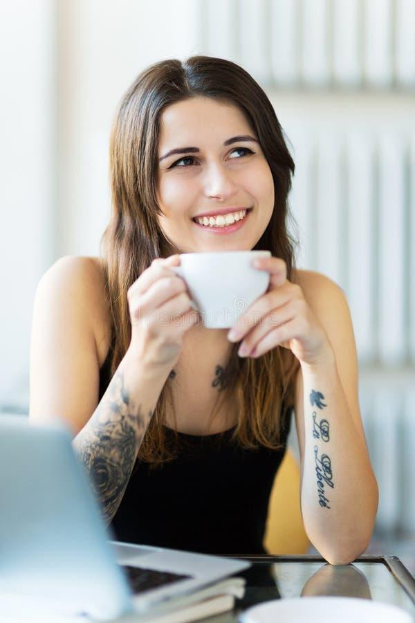 Tätowierte Frau, die einen Tasse Kaffee genießt lizenzfreies stockfoto