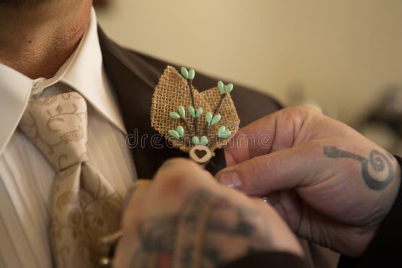 Tätowierte Handstiftleinwandcorsage auf Bräutigam lizenzfreie stockfotografie
