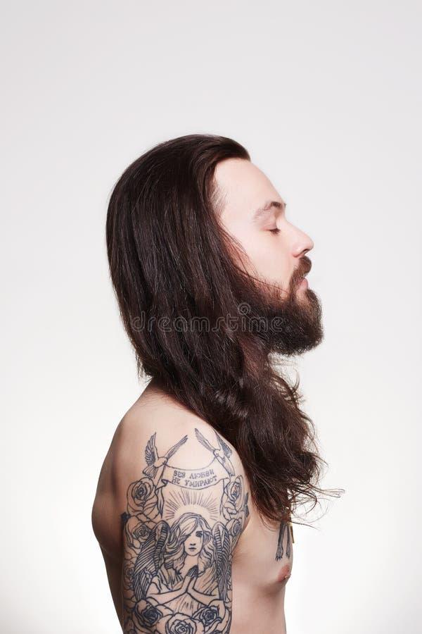 Tätowierter hübscher bärtiger Mann mit dem langen Haar stockfotografie