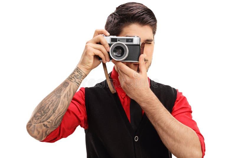 Tätowierter Mann mit einer Retro- Kamera lizenzfreie stockfotos