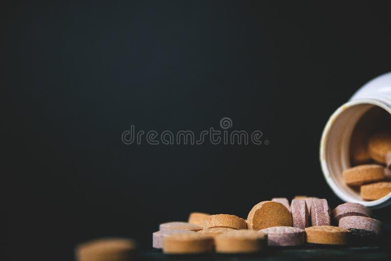 Tätt av behandla som ett barn upp vitaminer, och tillägg, underhåller immunitet på en mörk bakgrund med en vit flaska Inkludera v royaltyfri foto