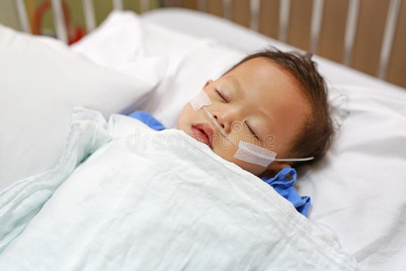 Tätt upp att behandla som ett barn pojken på tålmodig säng med röret i näsa för att leverera syre Respiratorisk service fotografering för bildbyråer