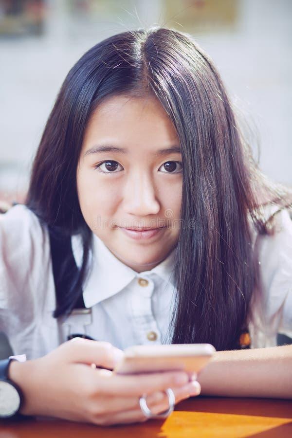 Tätt upp att vända mot asiatisk tonåringlycka som ler framsidan med smart p royaltyfria foton