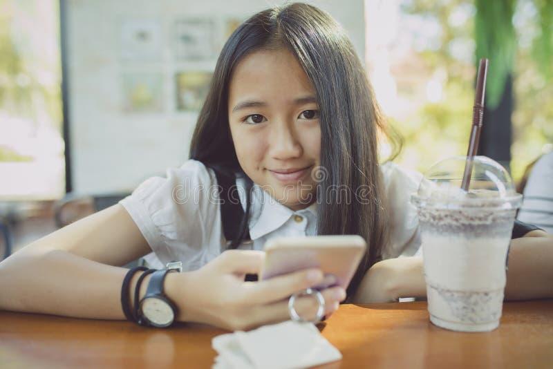 Tätt upp att vända mot asiatisk tonåringlycka som ler framsidan med smart p royaltyfri foto