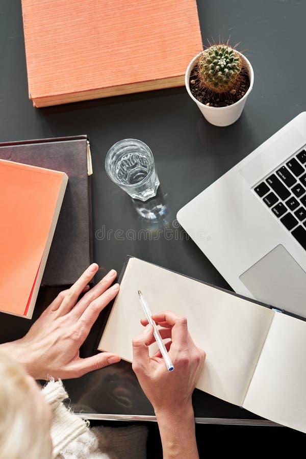 Tätt upp av kvinnas händer som gör anmärkningar på den vita spridda boken Kaktus och exponeringsglas av vatten Ung kvinna eller s arkivfoton