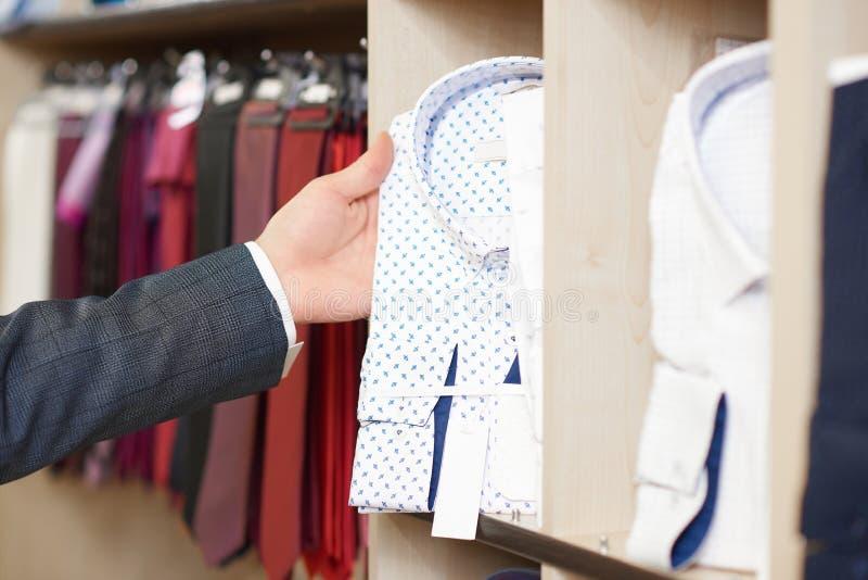 Tätt upp av mans hand som rymmer den vita skjortan i blå modell royaltyfri fotografi