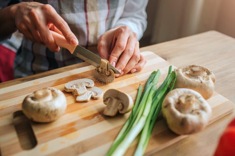 Tätt upp av mans kniven för handinnehav och klippachampinjonen Kvinnahjälp honom med att laga mat Hon sitter på tabellen Isolerat arkivfoto