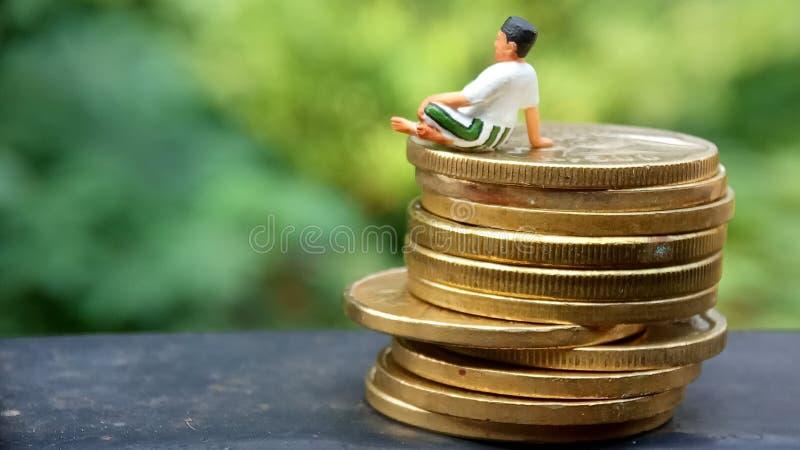 Tätt upp begreppsmässig, åldrades Midle mannen för att tycka om hans tjänar, eller inkomst, sitter på bunten av 500 guld- mynt, m royaltyfria bilder