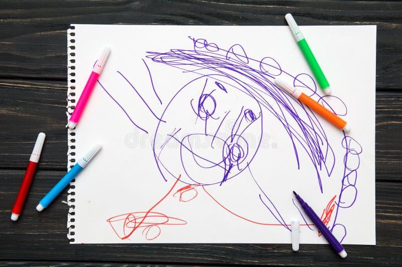 Tätt upp, lägger makroen, lägenhet Diagram som dras av ett årigt barn 3 Svart tabell med ett vitt ark av papper På det dras royaltyfri foto