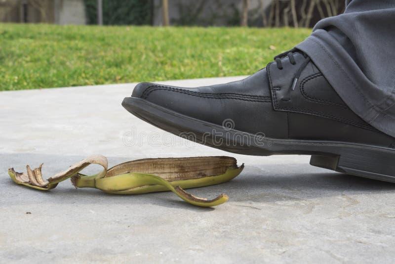 Tätt upp, piskar mannen med svart skon som kliver på bananen, skalar arkivbilder
