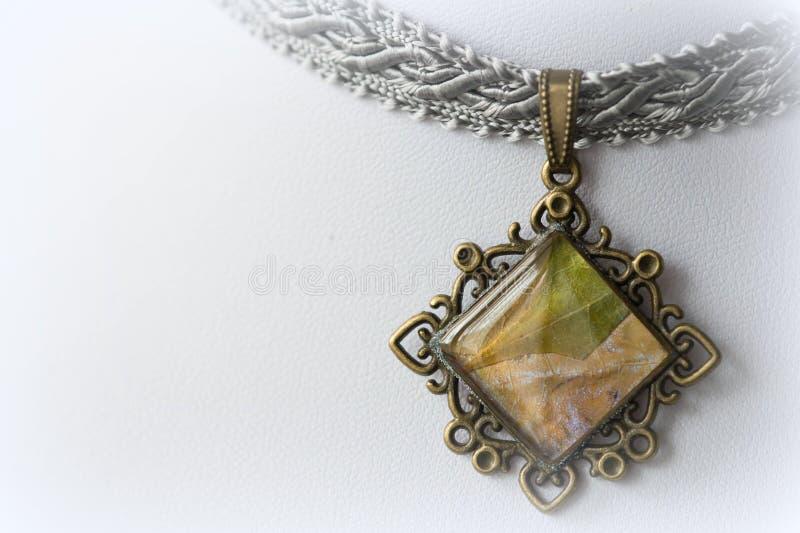 Tättsittande halsband-halsband med en hänge som göras av epoxykåda och lönnlöv royaltyfri bild