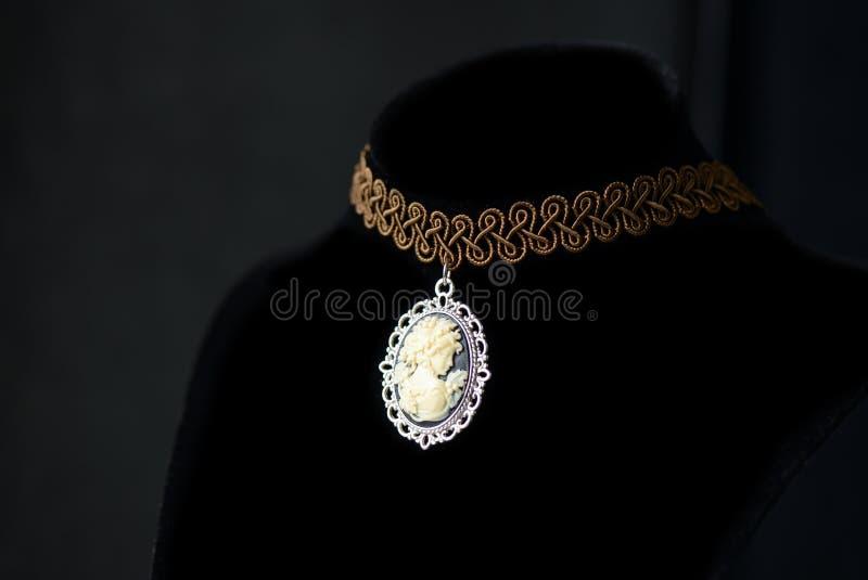 Tättsittande halsbandhalsband med flickakaméhängen på en mörk bakgrund royaltyfri bild